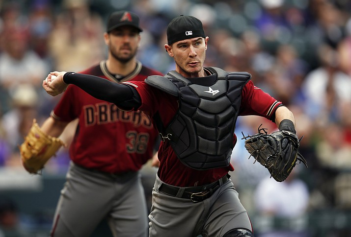 Arizona Diamondbacks catcher Chris Herrmann throws to first to put out Colorado Rockies' Chad Bettis after he put down a sacrifice bunt Wednesday, May 11, in Denver.