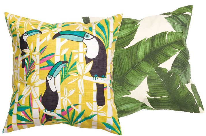 Playful toucans peek out from behind bamboo branches on a whimsical, tropical print throw pillow, left, and a vintage-style palm leaf print graces a chic throw pillow, right, both from H&M Home.