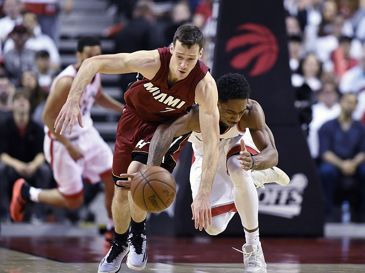 Miami Heat's Goran Dragic, left, and Toronto Raptors' DeMar DeRozan battle for a loose ball during the second half of Game 7 of the NBA basketball Eastern Conference semifinals in Toronto, Sunday, May 15.