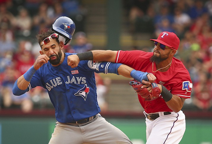Toronto Blue Jays Jose Bautista gets hit by Texas Rangers second baseman Rougned Odor after Bautista slid into second in the eighth inning at Globe Life Park in Arlington, Texas, Sunday, May 15.