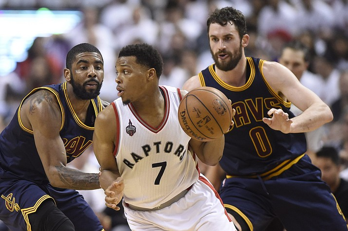Toronto Raptors guard Kyle Lowry, center, controls the ball as Cleveland Cavaliers forward Kevin Love, right, and guard Kyrie Irving defend during second half Eastern Conference final playoff basketball action in Toronto on Monday, May 23.