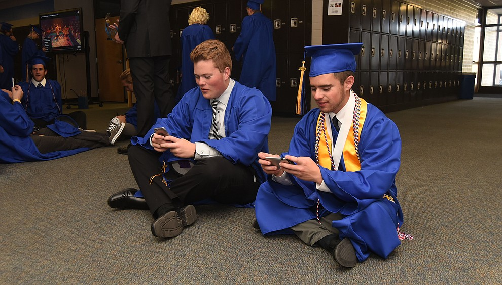 Jack Clark and Brandon Klever play a video game on their phones before Prescott High School holds their Commencement Ceremony for the Class of 2016 on May 27, 2016.  (Les Stukenberg/The Daily Courier)