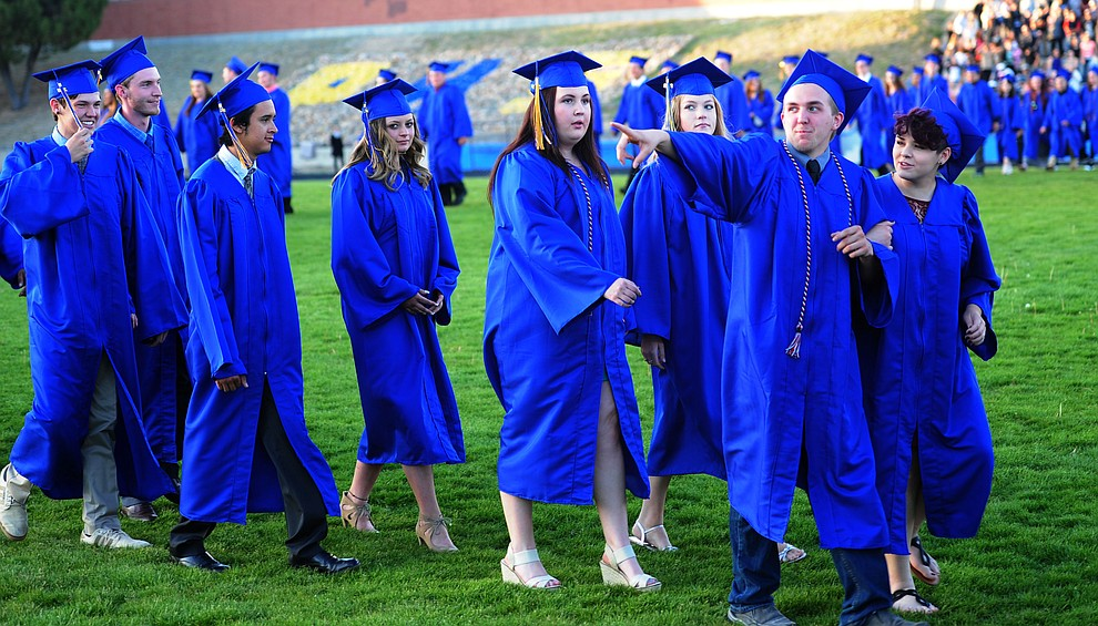 Students walk in the processional and wave to family and friends as Prescott High School holds their Commencement Ceremony for the Class of 2016 on May 27, 2016.  (Les Stukenberg/The Daily Courier)
