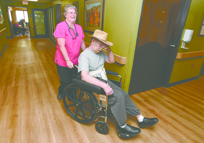 Mary Dennis wheels patient Mel Rouse to his room at the Prescott Nursing and Rehabilitation Center in Prescott.  Dennis received the Community Healthcare Scholarship in 2012 and has remained in the area working in the healthcare industry.
