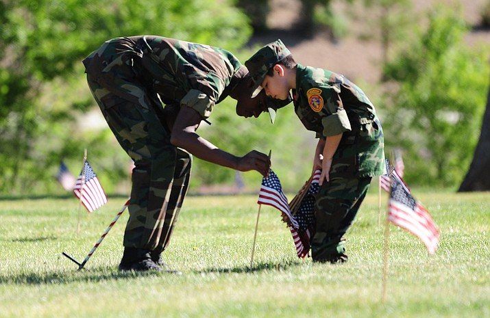Young Marines Charles Nnantah Jr. and Oscar Guerrero and other volunteers place flags at each headstone at the Prescott National Cemetery near the VA Hospital Saturday morning. The National Cemetery Administration (NCA) will conduct a Memorial Day ceremony today, May 30, at 11 a.m. at the Prescott National Cemetery.
