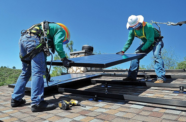 Edgar Soto and Juan Jamoa with SolarCity install solar panels on the roof of a home south of Prescott in 2012. Part of Arizona Public Service's 2016 request would do away with the solar buyback program and change the reimbursements.