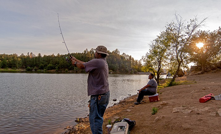 Luis Mendoza, left, casts his line into Goldwater Lake in June 2015 while Mike Talayumptewa waits for a bite. Novice anglers can catch their first fish with Arizona Game and Fish department help this Saturday, June 4, at AZGFD's ninth annual First Fishing Clinic.