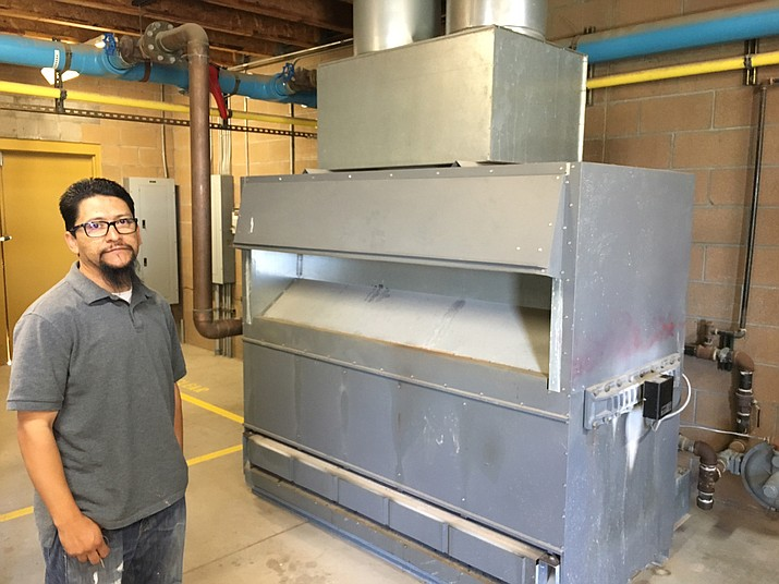 Chino Valley Aquatics Center Manager David Jaime stands in front of the broken heater that has delayed the opening of the town's pool. Temperatures are expected to exceed 100 degrees in Chino Valley this weekend.