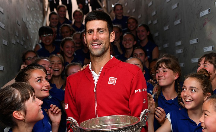 Novak Djokovic is cheered by ball girls after defeating Britain's Andy Murray in their final match of the French Open at the Roland Garros stadium, Sunday, June 5, in Paris.
