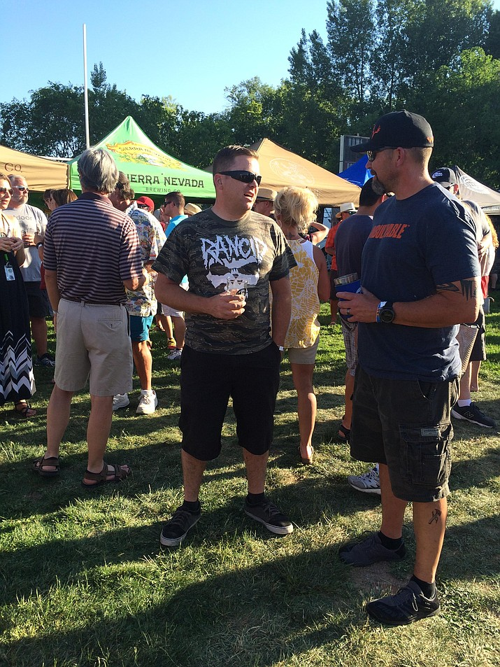 Nathan Artlip of Prescott enjoys a beer while catching up with fellow Prescott resident Jim Richardson at the Party in the Pines event on Saturday.