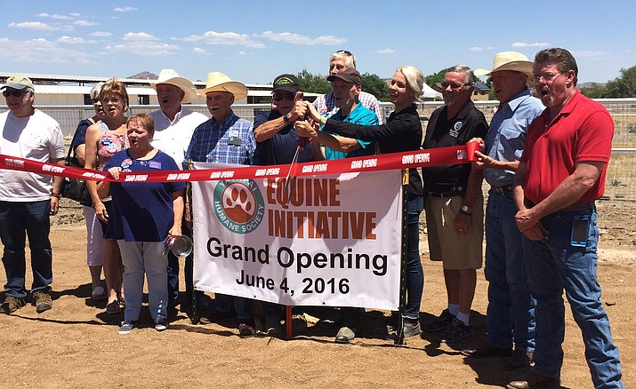 A group of supporters and local officials cut the ribbon on the new Yavapai Humane Society Equine Initiative. Dr. Steven Dow, a semi-retired veterinarian who will be providing medical care for the horses; Yavapai Humane Society Executive Director Ed Boks and Program Director Nina Ekholm Fry manage the Red Ribbon cutting scissors.