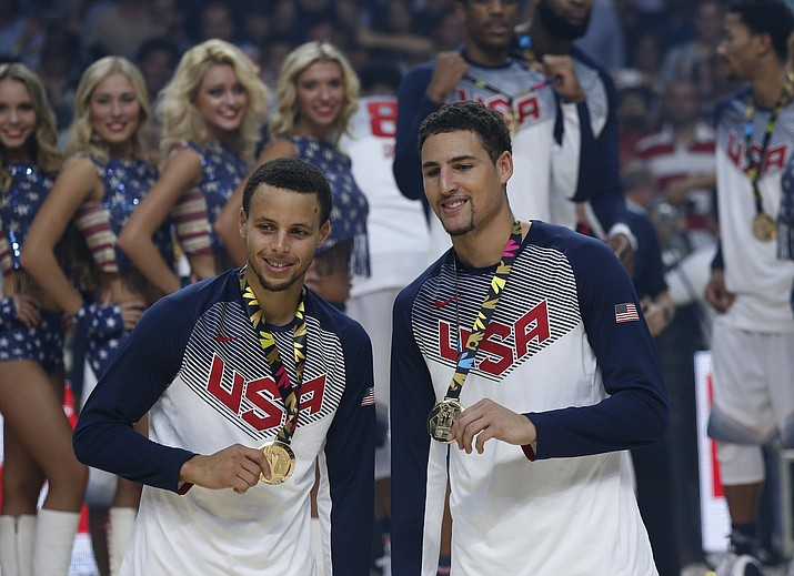 """United States' Stephen Curry, left, and Klay Thompson celebrate after wining the 2014 final World Basketball match against Serbia at the Palacio de los Deportes stadium in Madrid, Spain. Curry has withdrawn from consideration from the Olympics, leaving the U.S. basketball team without the NBA's MVP. Curry says Monday, June 6, in a statement that he has decided to pull out for """"several factors — including recent ankle and knee injuries."""""""
