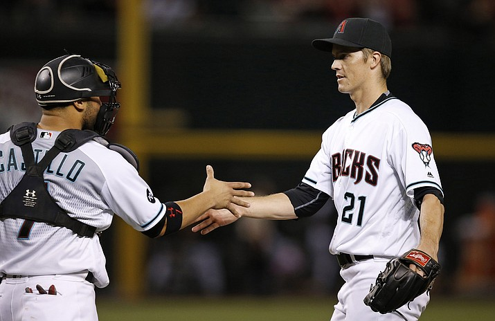 Arizona Diamondbacks pitcher Zack Greinke (21) shakes hands with catcher Welington Castillo, left, to celebrate a complete game shutout after the final out of a baseball game Tuesday, June 7, 2016, in Phoenix.  The Diamondbacks defeated the Rays 5-0. (Ross D. Franklin/Associated Press)