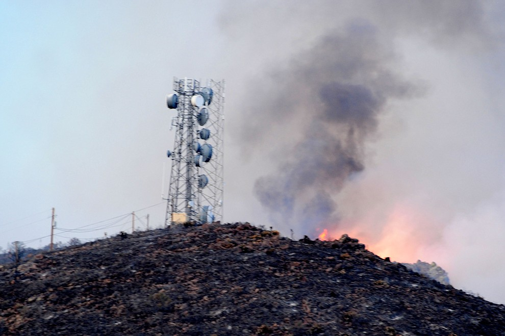 Fire burns around the communication tower and through the hills on the south side of Yarnell Wednesday afternoon. (Les Stukenberg/The Daily Courier)