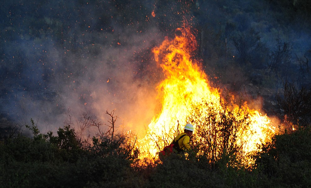 A firefighter works a hot spot as fire burns through the hills on the south side of Yarnell Wednesday afternoon. (Les Stukenberg/The Daily Courier)