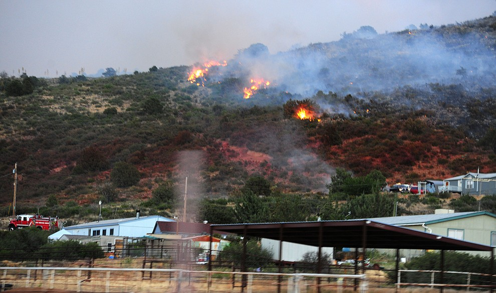 Fire burns but a line of slurry saved homes through the hills on the south side of Yarnell Wednesday afternoon. (Les Stukenberg/The Daily Courier)