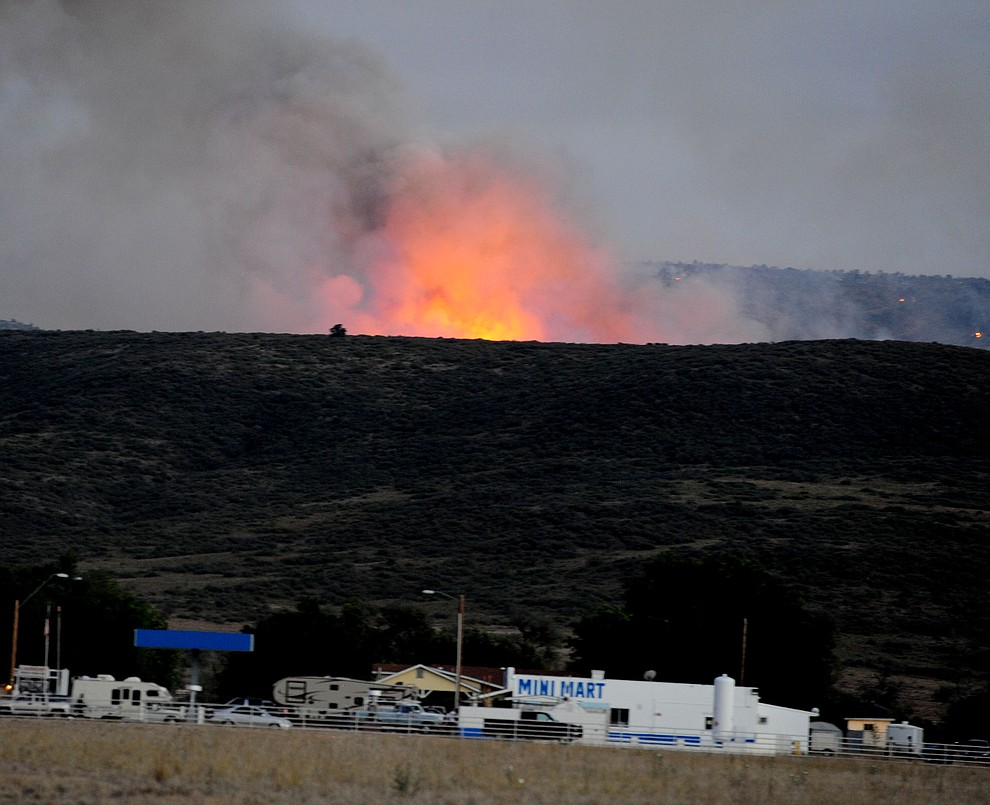 Fire glows over the Peeples Valley Mini Mart through the hills on the south side of Yarnell Wednesday afternoon. (Les Stukenberg/The Daily Courier)