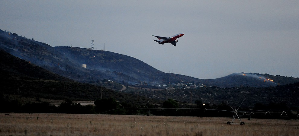 The DC10 makes a retardent drop as ight settles in over Yarnell as fire burns through the hills on the south side of Yarnell Wednesday. (Les Stukenberg/The Daily Courier)