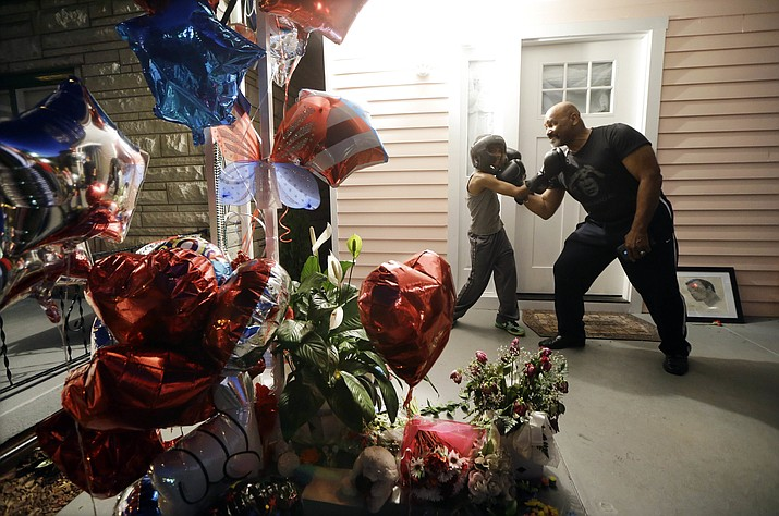 Walter Farrow Jr., right, of Birmingham, Ala., strikes a boxing pose with Malachi Chism, 10, of Louisville, Ky., on the porch of Muhammad Ali's boyhood home in Louisville on Thursday, June 9, 2016, the night before Ali's funeral and memorial services.