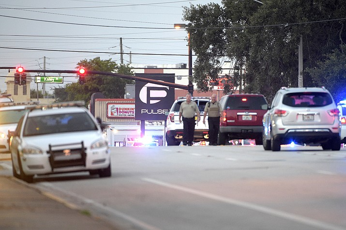 Police cars surround the Pulse Orlando nightclub, the scene of a fatal shooting, in Orlando, Fla., Sunday, June 12.