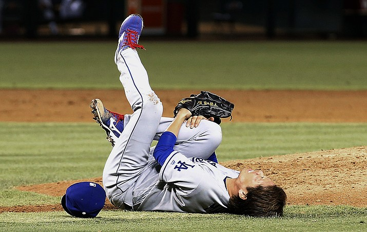 Los Angeles Dodgers' Kenta Maeda grabs his right leg after being hit by a batted ball by Arizona Diamondbacks' Paul Goldschmidt during the sixth inning Tuesday, June 14, in Phoenix. The injured Maeda had to leave the game.
