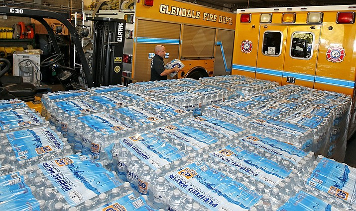 Glendale Fire Department firefighter Chris Greene carries a case of water as he walks past dozens of cases of water at the Glendale Fire Department Resource Center in preparation for record-setting heat expected over the weekend and into next week Thursday, June 16, 2016, in Glendale, Ariz.