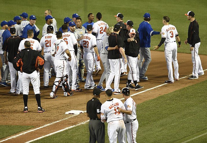 Baltimore Orioles manager Buck Showalter, right, calls to Manny Machado, foreground, after the benches cleared after Kansas City Royals pitcher Yordano Ventura threw a pitch at Machado in the fifth inning of a baseball game, Tuesday, June 7, in Baltimore.