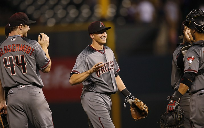 Arizona Diamondbacks shortstop Nick Ahmed, center, smiles as he is congratulated by first baseman Paul Goldschmidt, left, and catcher Welington Castillo after the Diamondbacks retired the Colorado Rockies in the ninth inning of a baseball game Thursday, June 23, in Denver. The Diamondbacks won 7-6 on an RBI-single hit by Ahmed.