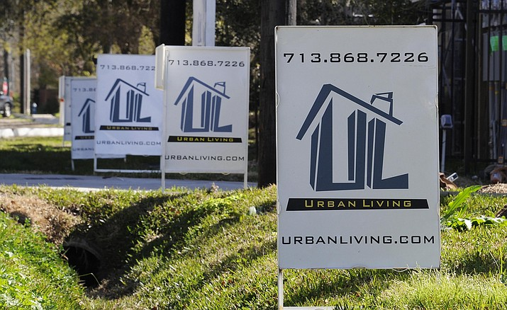 "In this Feb. 16 file photo, ""For Sale"" signs are stacked up outside a new complex of townhouses in Houston. Americans still want to own homes — if they can afford to. That's the finding of a report released Wednesday, June 22, by the Harvard University Joint Center for Housing Studies."