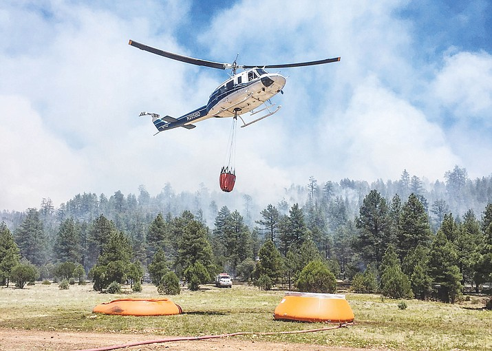 A helicopter reloads for another drop on the Cedar Fire, burning southwest of Show Low and Pinetop-Lakeside, Arizona. Of the 29 wildfires currently burning in the state, the Cedar Fire is the largest at more than 45,000 acres. It is 24 percent contained.