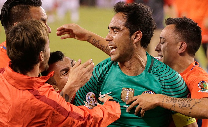 Teammates hug Chile goalkeeper Claudio Bravo after defeating Argentina in the Copa America Centenario championship soccer match, Sunday, June 26, in East Rutherford, N.J.