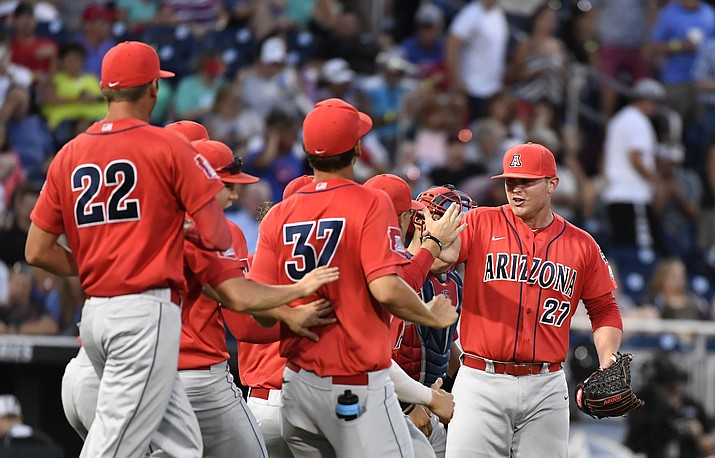 Arizona pitcher JC Cloney (27) celebrates beating Coastal Carolina 3-0 in Game 1 of the NCAA Men's College World Series finals baseball game in Omaha, Neb., Monday, June 27.