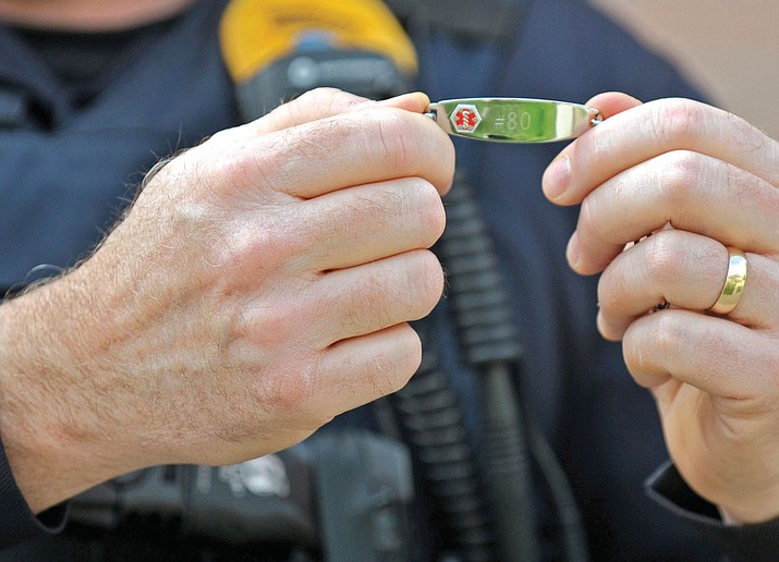 Prescott Police Sgt. Ben Scott holds up an Alzheimer's disease identification bracelet March 11, 2015, at the Prescott Police Department. Scott is the supervisor for the grant that is being used for the bracelets.