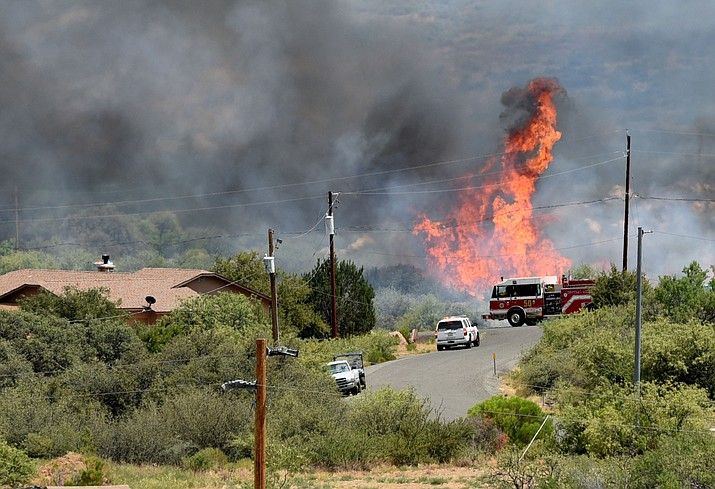 Brush burns near a home on the Bug Creek Fire near Cordes Lakes Tuesday afternoon, June 28.
