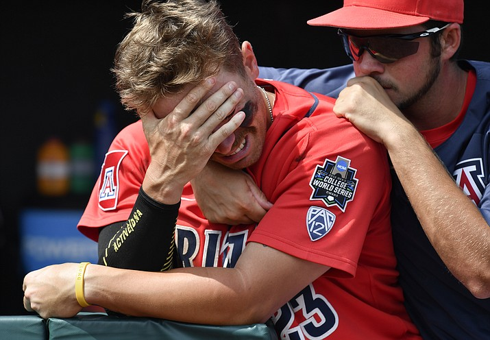 Arizona's Zach Gibbons is comforted by Ray McIntire after losing to Coastal Carolina 4-3 in Game 3 of the NCAA College World Series baseball finals in Omaha, Neb., Thursday, June 30.