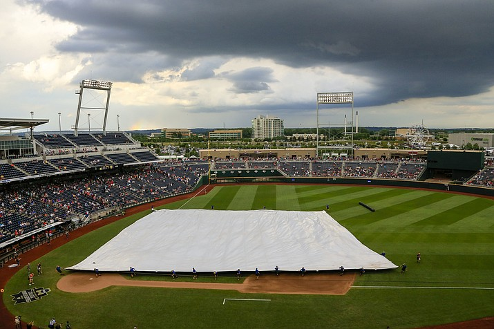 Grounds crew members pull the tarp over the playing field at TD Ameritrade Park during a weather delay before Game 3 of the NCAA College World Series finals between Coastal Carolina and Arizona in Omaha, Neb., Wednesday, June 29.