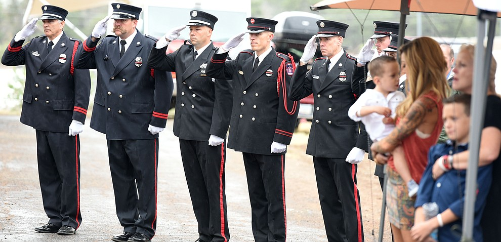 Honor Guard members salute during the reading of the names during a Celebration of Remembrance ceremony at the Arizona Pioneer's Home Cemetery on the third anniversary of the death's of the 19 Granite Mountain Hotshots while fighting the Yarnell Hill Fire. (Les Stukenberg/The Daily Courier)