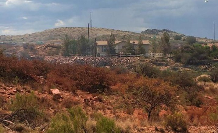 The land and brush surrounding homes in the Cordes Lakes area are stained red from slurry dropped to fight the Bug Creek Fire. No structures were lost in this wildfire, which torched 1,080 acres of grassland.