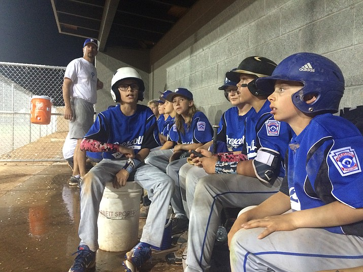 The Prescott All-Stars hang out in the dugout at Riverfront Park in Cottonwood after rain and lightning strikes forced umpires to clear the fields. Prescott leads the Wickenburg All-Stars 3-0, and play will resume Tuesday, July 5, in the top of the fifth inning.