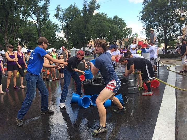 Tyler Blackmore of the Prescott Fire Explorers transfers a bucket of water during the Bucket Brigade competition in downtown Prescott on Sunday morning, July 3. The brigade is a part of the annual Hose Cart Races that take place over the Fourth of July weekend.