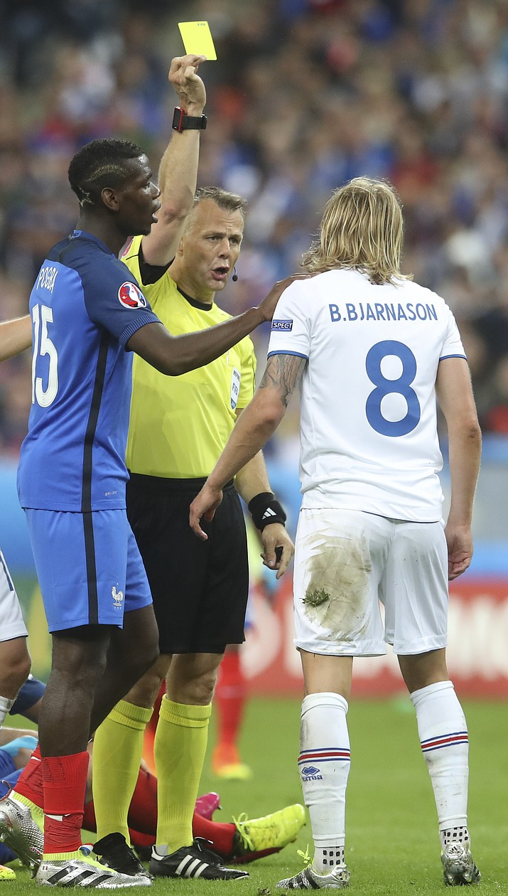 Iceland's Birkir Bjarnason, right, receives a yellow card from referee Bjorn Kuipers during the Euro 2016 quarterfinal soccer match between France and Iceland, at the Stade de France in Saint-Denis, north of Paris, France, Sunday, July 3.