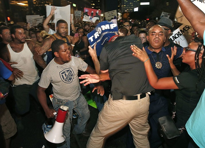 Rev. Jarrett Maupin, second from right, stands his ground as a Republican presidential candidate Donald Trump supporter, center, tries to interrupt marchers, as they take to the streets to protest against the recent fatal shootings of black men by police Friday, July 8, 2016, in Phoenix.