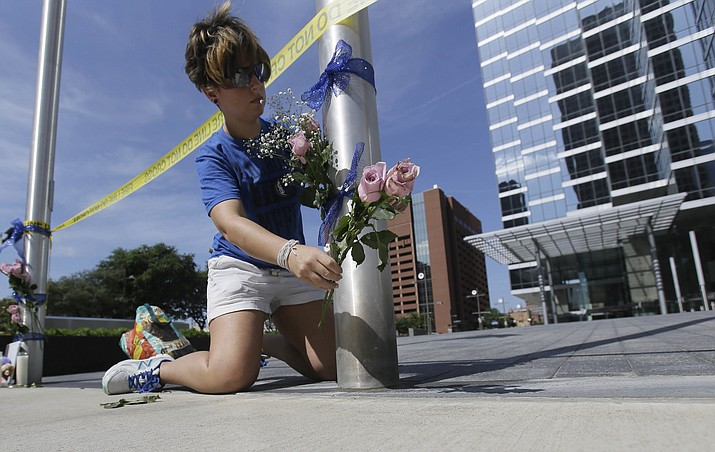 Noelle Hendrix places flowers near the scene of a shooting in downtown Dallas, Friday, July 8, 2016. Snipers opened fire on police officers in the heart of Dallas during protests over two recent fatal police shootings of black men.