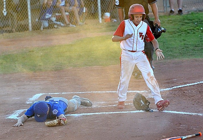 Prescott All-Stars starting pitcher Tyson Potts lays face down in the dirt after a Verde Valley runner scores in the first inning of the District 10 Majors All-Stars Tournament championship game Friday night at Riverfront Park in Cottonwood. (Vyto Starinskas/Special To The Courier)
