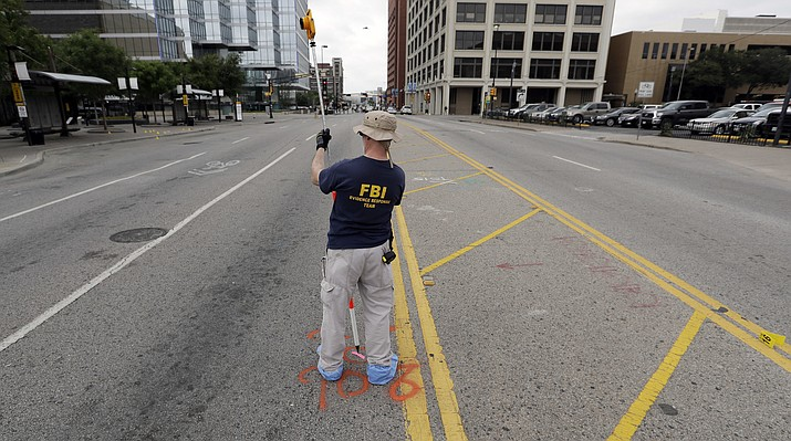 Investigators work in the area of downtown Dallas that remains an active crime scene, Saturday, July 9, 2016. Micah Johnson, an Army veteran, opened fire on police officers in the heart of Dallas Thursday, as hundreds of people were gathered to protest two recent fatal police shootings of black men, Philando Castile and Alton Sterling.