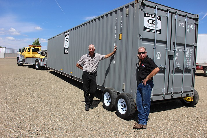 Gary Gates (left) and Chris Christiansen stand next to a storage container they just turned into a trailer using their new invention.