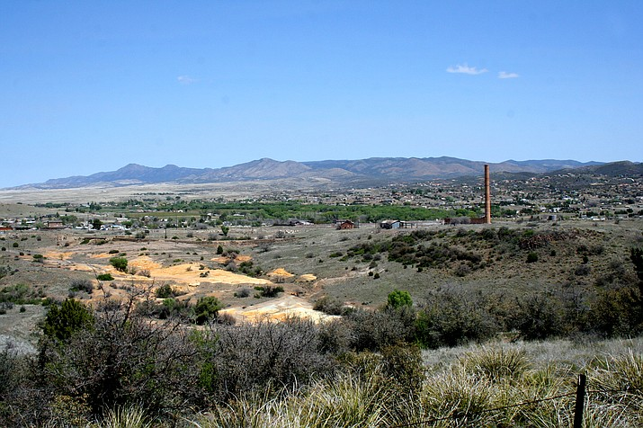 Contamination from historical mining, left, and the Humboldt smelter stack, right, remains cordoned off in Dewey-Humboldt as the Environmental Protection Agency studies its reach and potential risk over the past 10 years in this 2015 photo. EPA anticipates a revised report by Fall 2016 with plans on how to remediate this property and the Iron King Mine Superfund site.