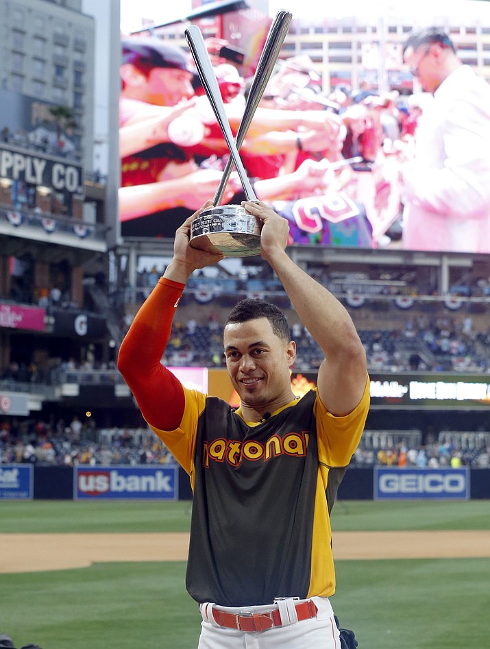 National League's Giancarlo Stanton, of the Miami Marlins, holds the champions trophy after the All-Star Home Run Derby on Monday in San Diego.