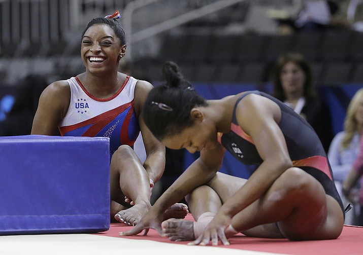 Simone Biles, left, smiles next to Gabrielle Douglas while stretching during practice at the U.S. Olympic trials in gymnastics in San Jose, Calif., Thursday, July 7. Biles was the All-Around winner Sunday.