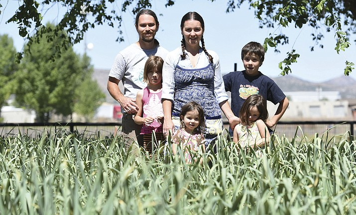 Chris and Sarah Reckards, who have been hired to run the Yavapai County Grown CSA Farm, pose with their family - Samuel, Ariyah, Soraya and Isabella - in their home garden called Loves Gathering in Chino Valley.